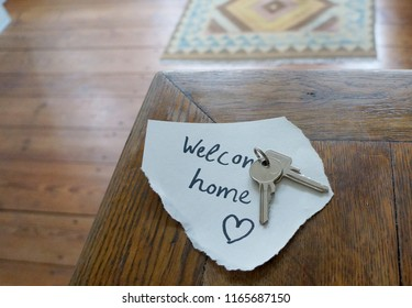 Note with welcome home written on it and keys on wooden table in minimalist room