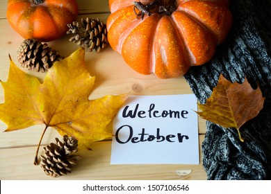 A note with Welcome October text on a rustic wooden table with Autumn decorations