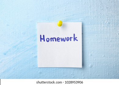 "Note with word ""Homework"" pinned to wall"