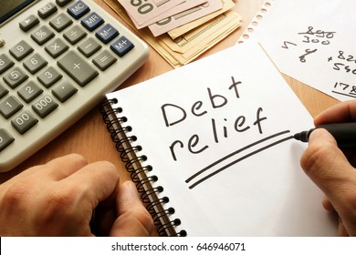 Note with words debt relief on a table.