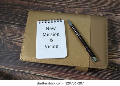 "A note written ""New Mission & Vission"" on table with organizer and pen"