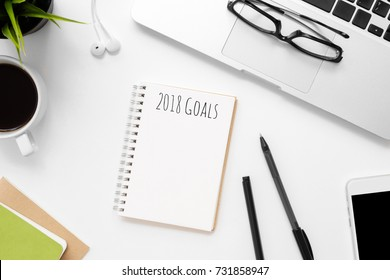 Notebook with 2018 Goals text on top of white office desk table with supplies. Top view, flat lay.