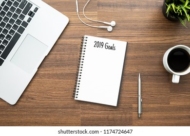Notebook with 2019 Goals text is on top of wood office desk table with supplies. Top view with copy space, flat lay.