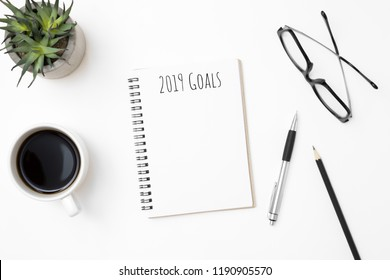Notebook with 2019 Goals text on top of white office desk table
