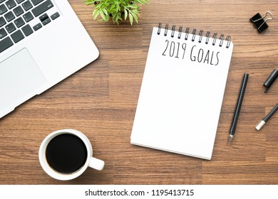 Notebook with 2019 Goals text on top of wood office desk table with supplies. Top view, flat lay new year resolutions concept.