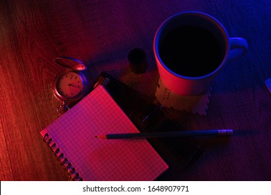 Notebook, antique clock, coffee and photographic film in neon light