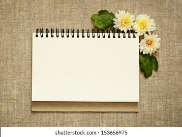 Notebook and asters in a corner on gray canvas background
