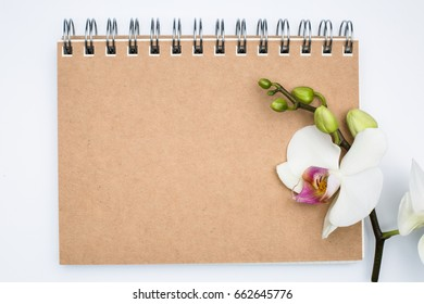 Notebook with a beautiful flower orchid, congratulations concept, Cardboard cover