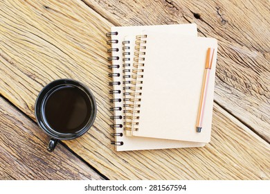 Notebook and  black coffee in black cup on wooden table