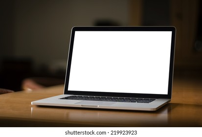 Notebook with blank screen on table in home interior
