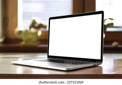 Notebook with blank screen on table in living room.