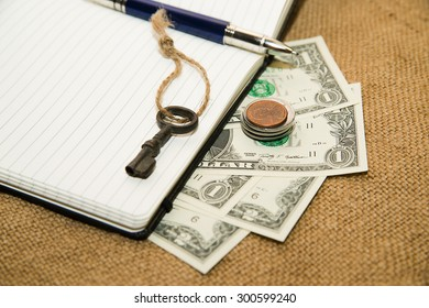 notebook with a blank sheet, pen, key and money on the old tissue