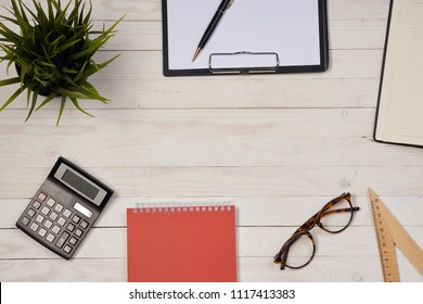 notebook and calculator, glasses and ruler on the table
