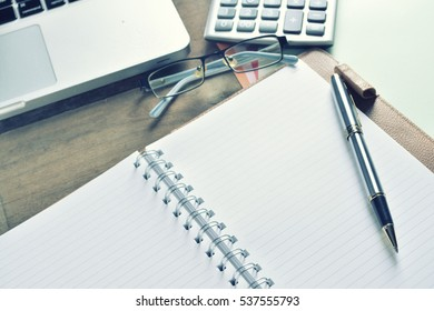 Notebook with calculator, keyboard and pen on table