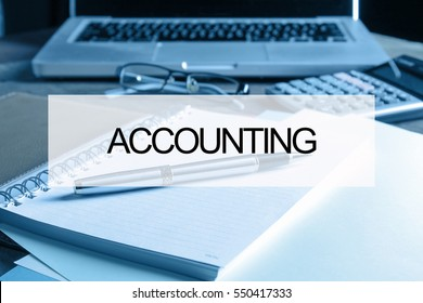 Notebook with calculator, keyboard and pen on table with text ACCOUNTING