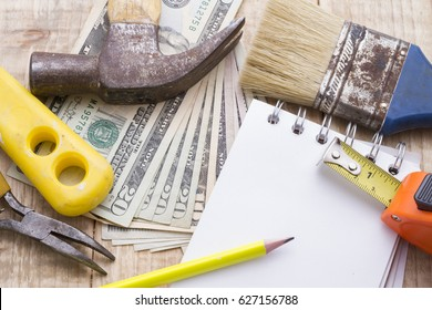 Notebook, calculator, and tools on wooden background to make a remodeling budget