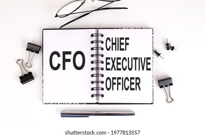 Notebook with CFO or Chief Financial Officer on the table with office tools