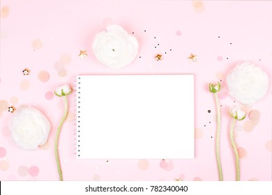Notebook with clean page with beautiful spring ranunculus flowers on pink pastel background with sparkles. Top view. Flat lay style.