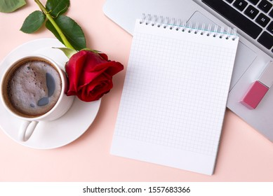notebook with a clean sheet on a laptop, lipstick, a Cup of black coffee, a red rose flower on a beige background