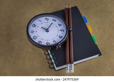 Notebook and clock,pencils