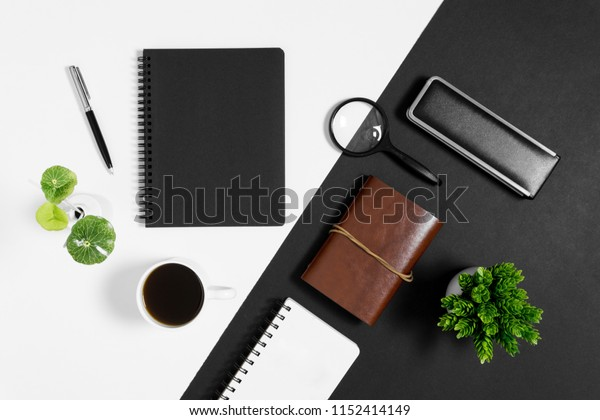 Notebook with coffee cup and personal items on black and white background.