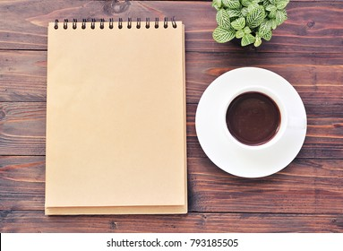 Notebook and coffee on wood background with copy space.