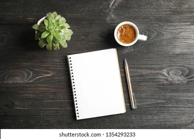 Notebook, coffee and plant on dark wooden background