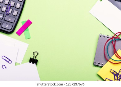 Notebook, colored bookmarks, elastics, clips and numbers on green background. Stationery and calculator. Business cards with copy space and binders near sticky notes and puncher. Business idea concept