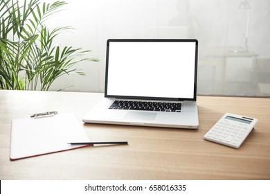 Ein Notebook mit Klemmbrett, Taschenrechner auf dem Holzschreibtisch im Büro.