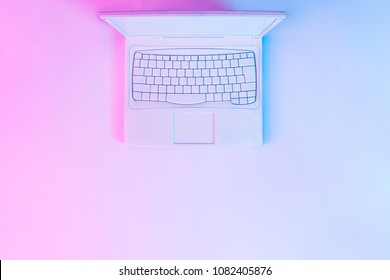 Notebook computer or laptop painted in white with vibrant bold gradient purple and blue holographic color lights. Concept art. Minimal office surrealism.