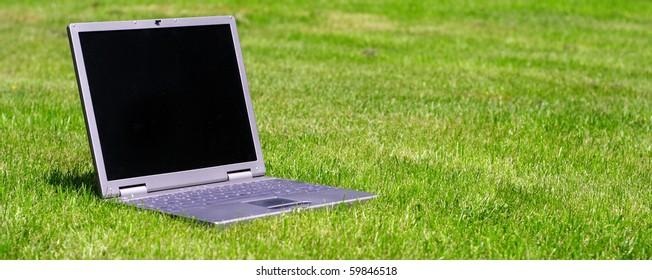 Notebook computer lying on green grass.