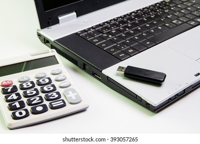 Notebook computer on the desk.Calculators,USB flash drive stick