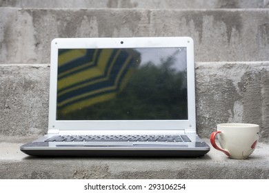 Notebook computers placed on concrete stairs. And the screen is blurred reflection of umbrellas and trees.