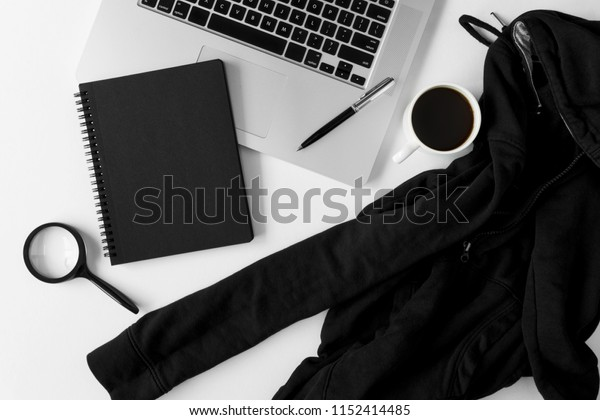 Notebook with copy space, sweater and laptop on white office table.