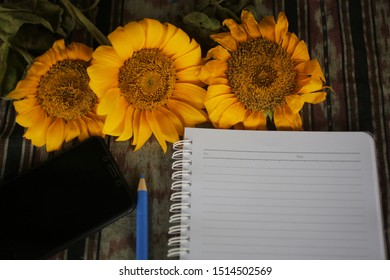 Notebook crop, sunflower and pen on classic fabric background. Office flat lay concept. Copy space for text and design.