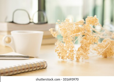 Notebook with cup of coffee and beautiful flower on working desk