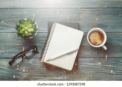 Notebook and cup of strong coffee on wooden background.