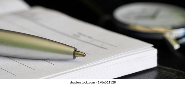 A notebook or diary, a ballpoint pen and a wrist watch are on a black table. Concept of memoir, bequest or daily routine planning. Web banner. Selective focusing. Macro