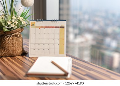 Notebook diary with pencil vase on table with January 2019 calendar at office work place with blurred background. Planning scheduling agenda event timeline payment reminder. Calendar 2019 concept.