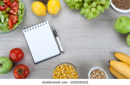 notebook with a diet nutrition with fresh vegetables and fruits on the table top view