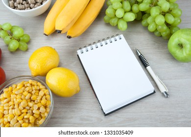 notebook with a diet plan with fresh vegetables and fruits on the table close up