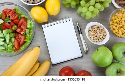 notebook with a diet plan with fresh vegetables and fruits on the table top view