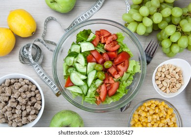 notebook with a diet plan with fresh vegetables and fruits and a side dish on the table top view