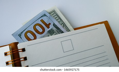 Notebook with dollars. Spiral notepad on a table with hundred dollar bills attached to it. Businessman Diary, Calendar to plan cases or meetings for the day or month.Template with empty paper pages.