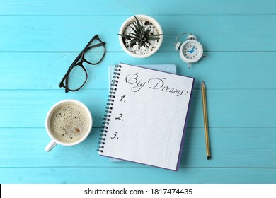 Notebook with dreams list on turquoise wooden table, flat lay