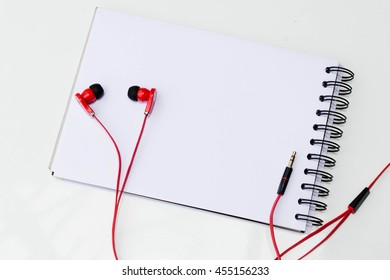 notebook, ear phone and red things.