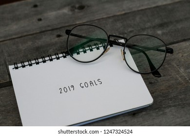 Notebook and eye glasses over the wooden table written 2019 GOALS