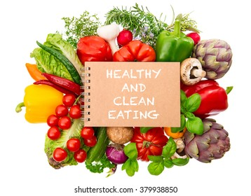 Notebook with fresh organic vegetables and herbs closeup isolated on white background. Healthy and clean eating concept