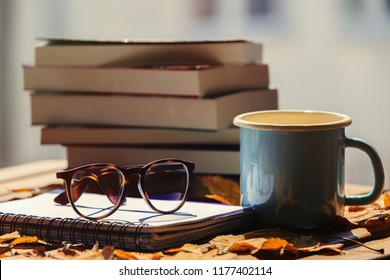 Notebook with glasses cup and books, maple leaves on wooden table. Side view. Fall season