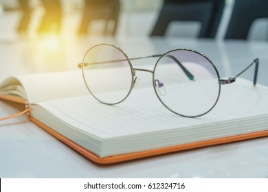 Notebook and glasses on meeting room.